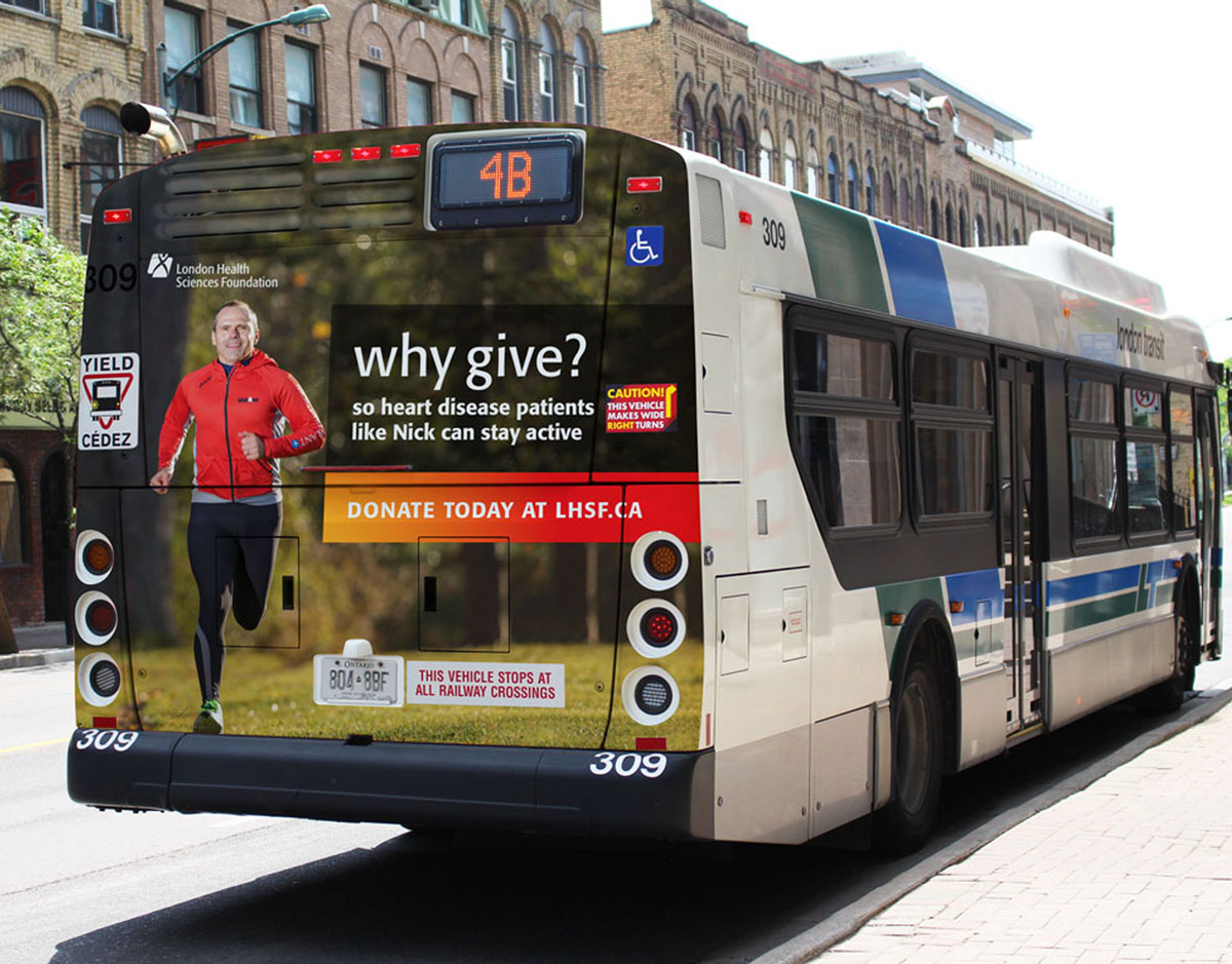 Why Give bus back advertisement on a London Transit bus driving down the street.