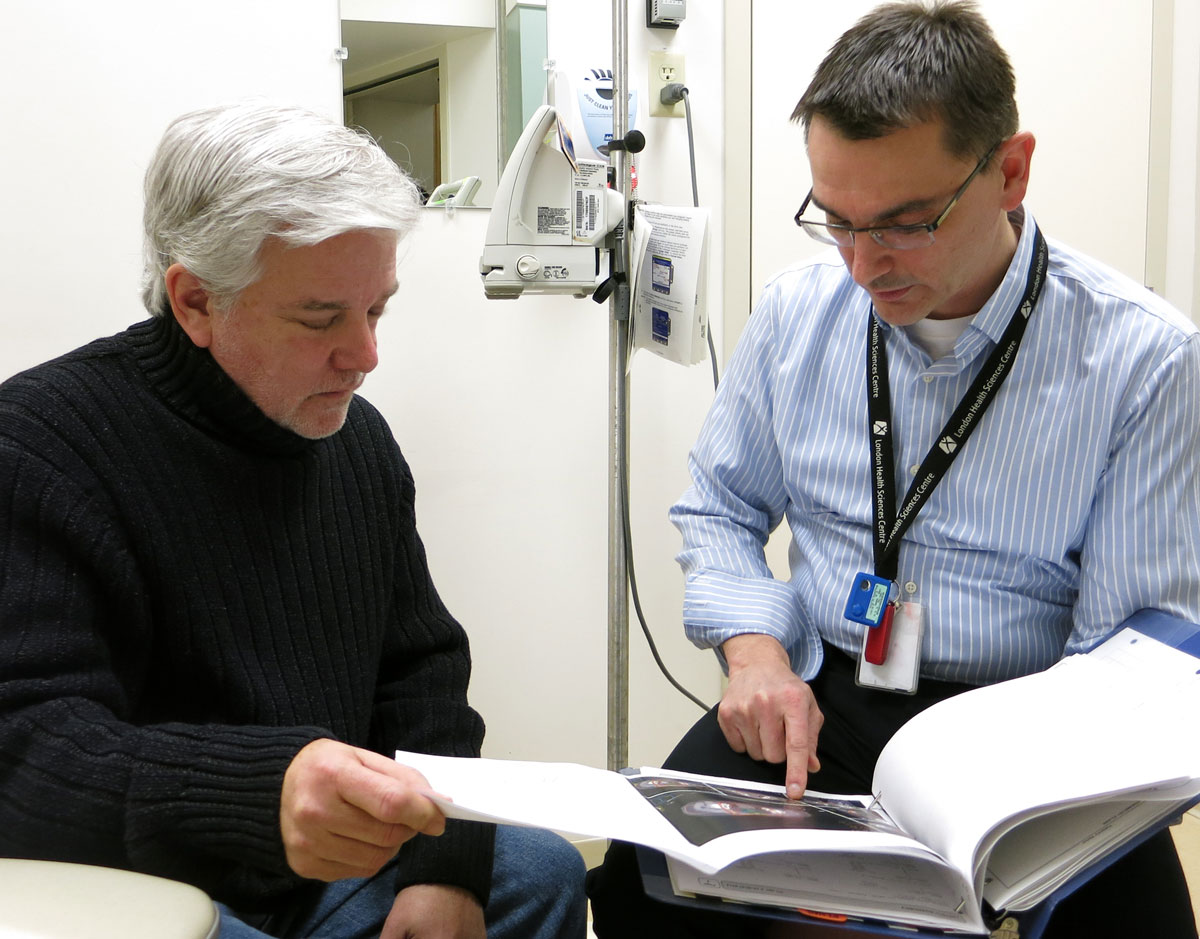 Male physician pointing to a photo in a book with a male client beside him.