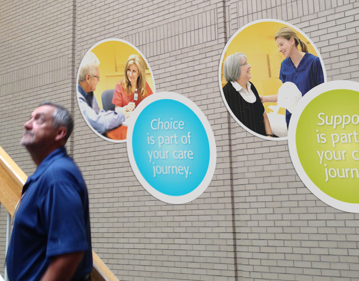 Male looking up at multiple circle decals on a brick wall with patient and nurse photos on them.