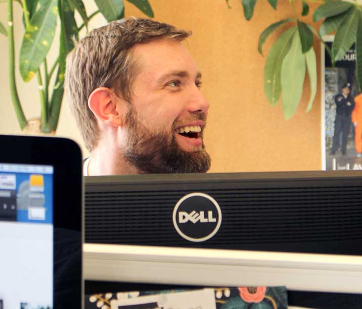 Digital designer, Ryan McLarty, sitting behind his computer, smiling and laughing while looking away from the camera.
