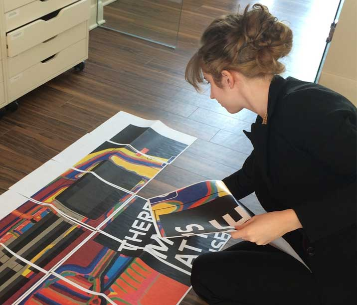 Graphic designer, Sarah Ross, putting papers together on the floor in the creative agency studio.